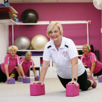 Pilates teacher demonstrating pose with midlife clients
